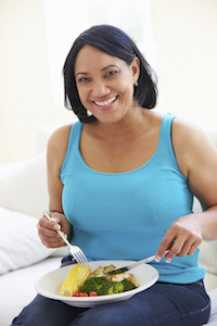 Overweight Woman Eating Healthy Meal Sitting On Sofa